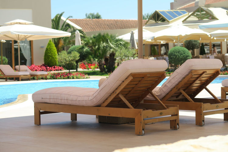 Hotel pool wooden deck chairs. Sunbeds by an open air pool at a luxury hotel resort in Halkidiki Greece. Beach Beds Chalkidiki Deck Chair Deck Chairs Furniture Halkidiki Hotel Pool Hotel Room Lux Luxury Outdoors Pool Poolside Poolside View Relaxation Resort Summer Sun Umbrella Sunbed Sunbeds Sunbeds And Umbrella Sunset Swimming Pool Tan White Umbrella