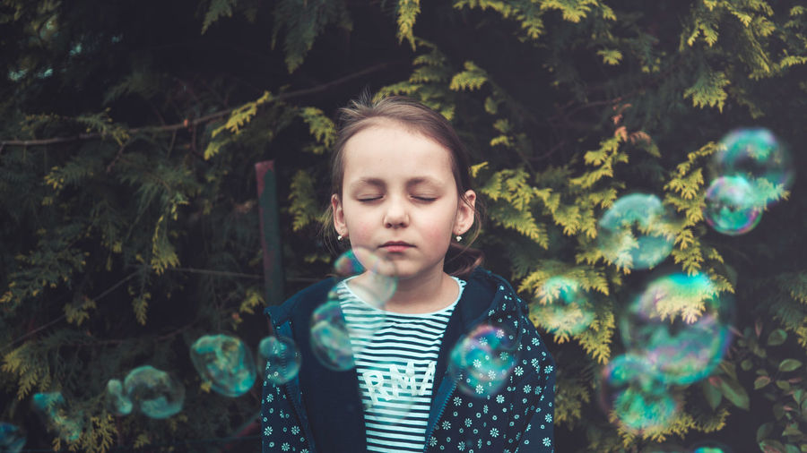 Girl With Closed Eyes Standing Amidst Bubbles Against Plants