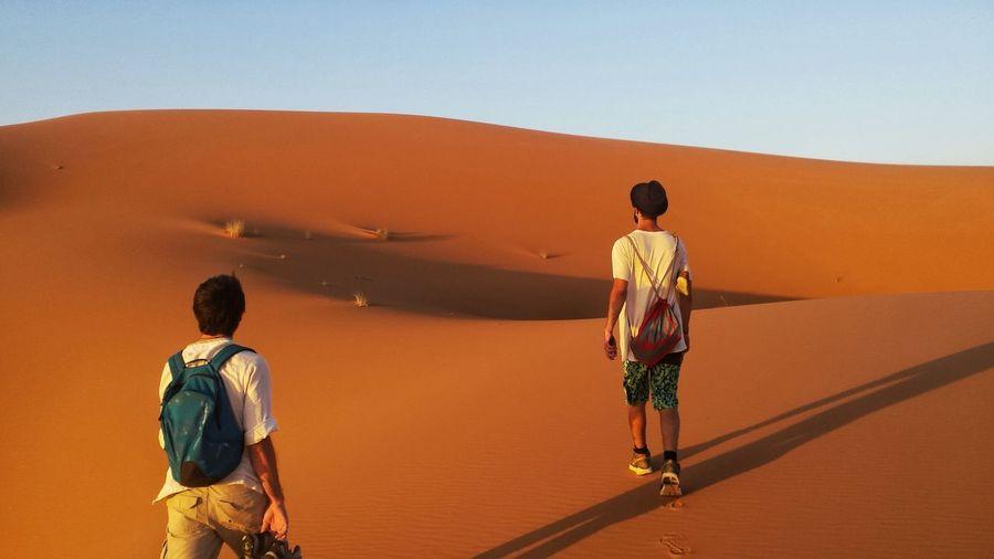 Rear view of men walking at desert during sunset