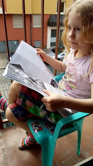 High angle view of little girl holding book while sitting on small chair in balcony