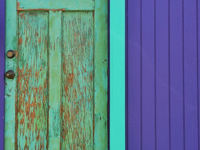 Weathered closed door on purple wall
