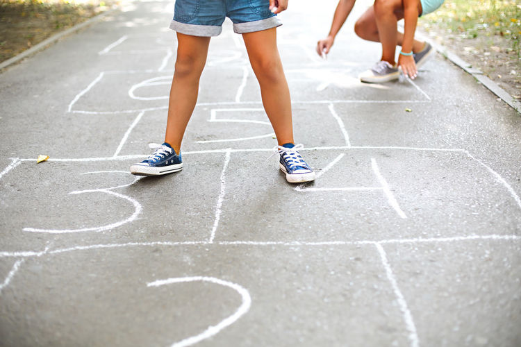 Low section of girls playing hopscotch on road