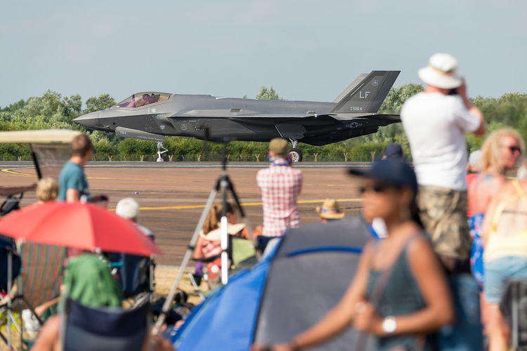 A Lockheed Martin F-35 Lightning II taxiing on the runway at RIAT Fairford 2018, UK, with spectators looking on. Air Tattoo Airshow F-35 Lightning Fairford Lockheed Lockheed Martin F-35 Lightning II RIAT Royal International Air Tattoo US Air Force Aerobatics Air Display  Aircraft Airplanes Aviation Fighter Jet Futuristic International Open Air Pilot Public Public Access Runway Spectators Taxiing Viewers War Plane Weekend Group Of People Real People Men Transportation Women Mode Of Transportation Lifestyles Day Adult Leisure Activity Nature Large Group Of People Group Incidental People Air Vehicle Crowd Outdoors Sky