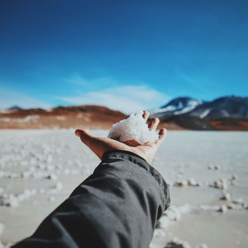 Cropped hand holding slat flat at atacama desert