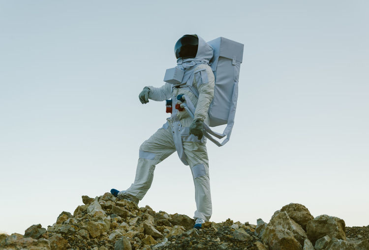 Low angle view of an astronaut standing on rock against clear sky