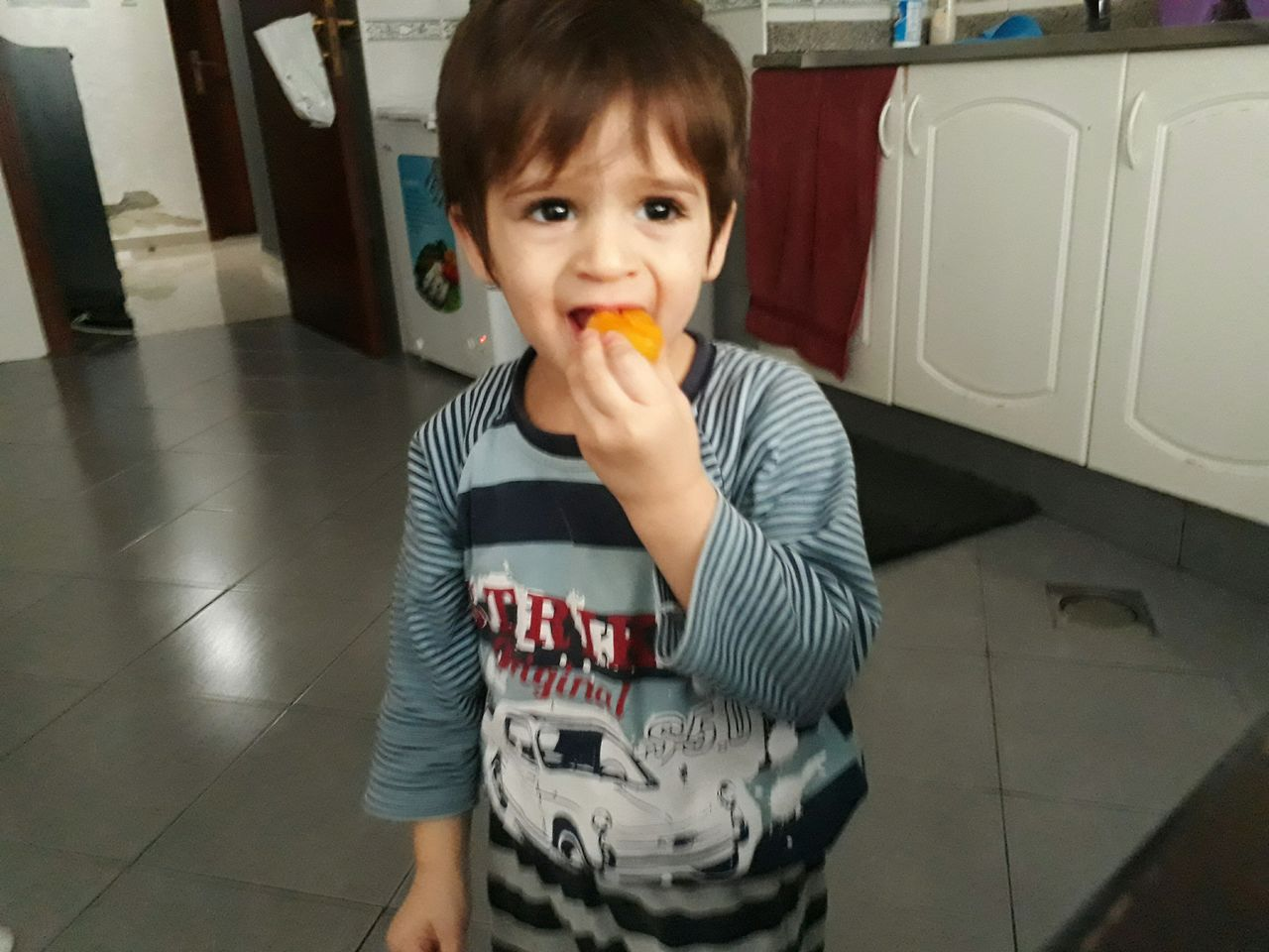 Boy Eating Food While Standing In Kitchen At Home