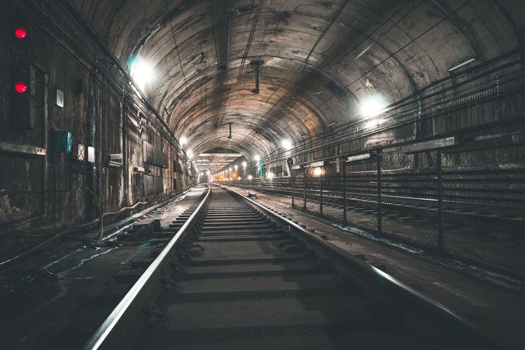 Railroad track in illuminated tunnel