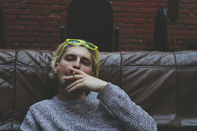 Portrait of man smoking cigarette while sitting on sofa against brick wall