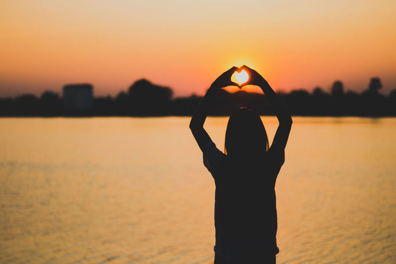 Silhouette woman making heart shape with hands by lake against sky during sunset