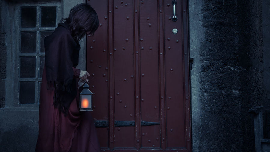 Side view of woman standing against closed door holding a light lantern