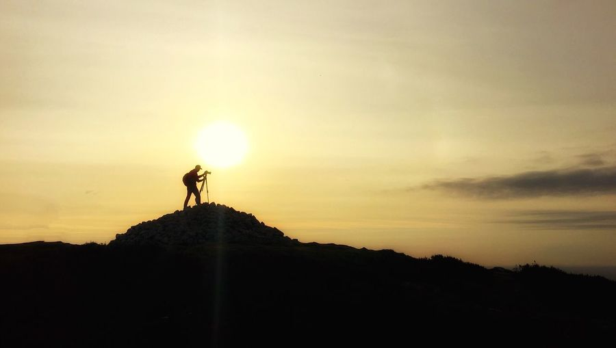 Silhouette man with tripod on rocks against sky during sunset