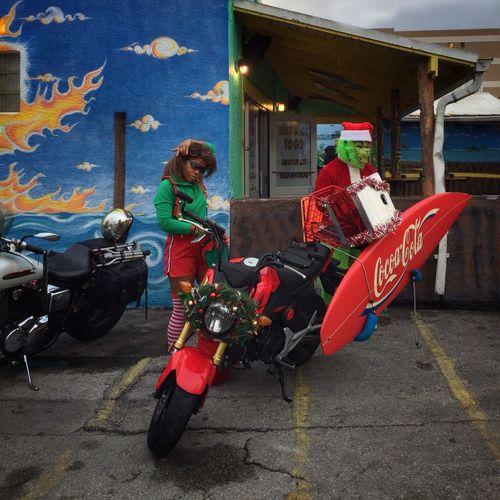 The grinch & an elf arrive Surfing Santas Cocoa Beach, Florida Two People The Grinch Santa's Helper Motorcycles Surf Board