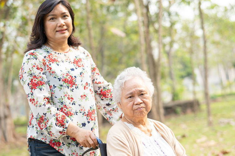 Portrait of smiling woman with handicapped mother on wheelchair against trees