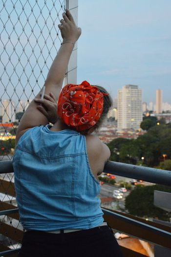 Close-up of red rose with city in background