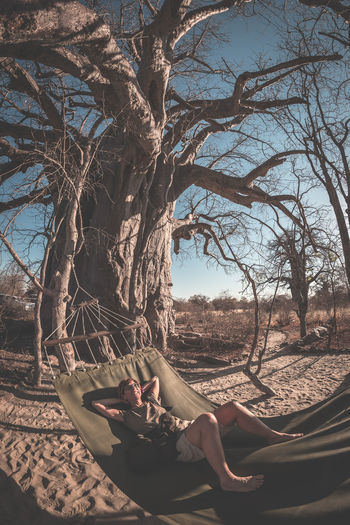 Couple taking selfie on hammock hanging from huge Baobab tree in the african savannah. Fisheye view, toned image. Wilderness safari and adventure in Africa. Bare Tree Beauty In Nature Branch Day Full Length Lifestyles Low Section Lying Down Nature One Person Outdoors Real People Relaxation Sitting Sky Tranquil Scene Tranquility Tree Tree Trunk Young Adult