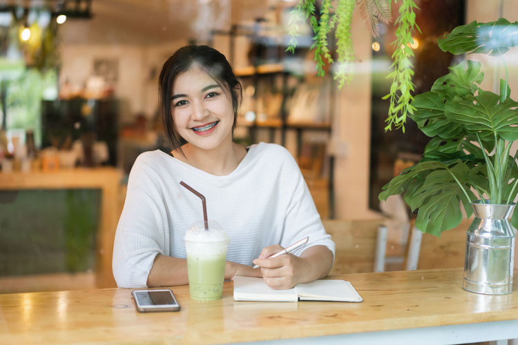Portrait of a smiling young woman at restaurant table