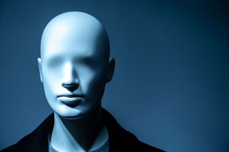 Close-up of mannequin against blue background