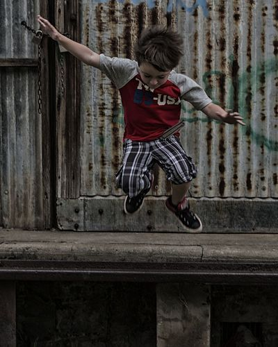 Full Length Of Boy Jumping Against Old Building