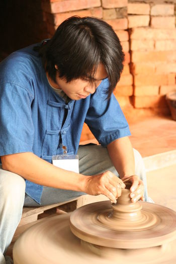 Casual Clothing Craft Day Leisure Activity Lifestyles Looking Down Portrait Potter Potters Wheel Relaxation Sitting Skill  Thailand Working Young Man