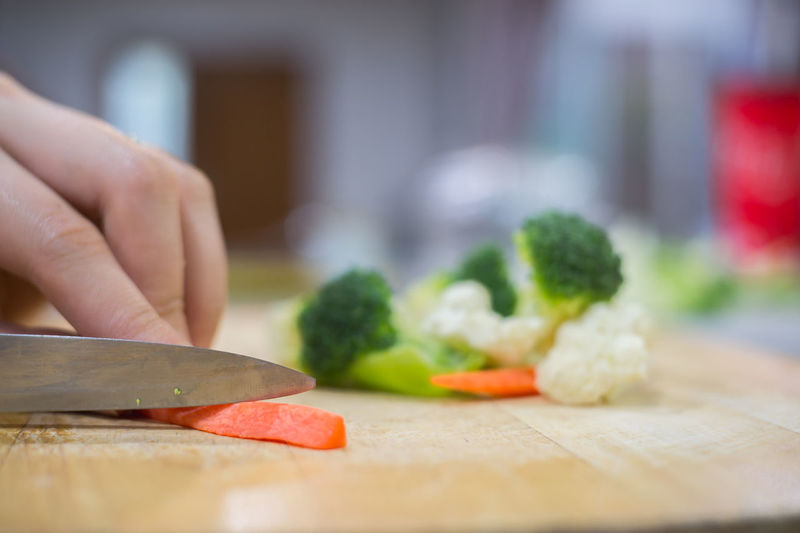 Cropped Hand Cutting Vegetables On Kitchen Island