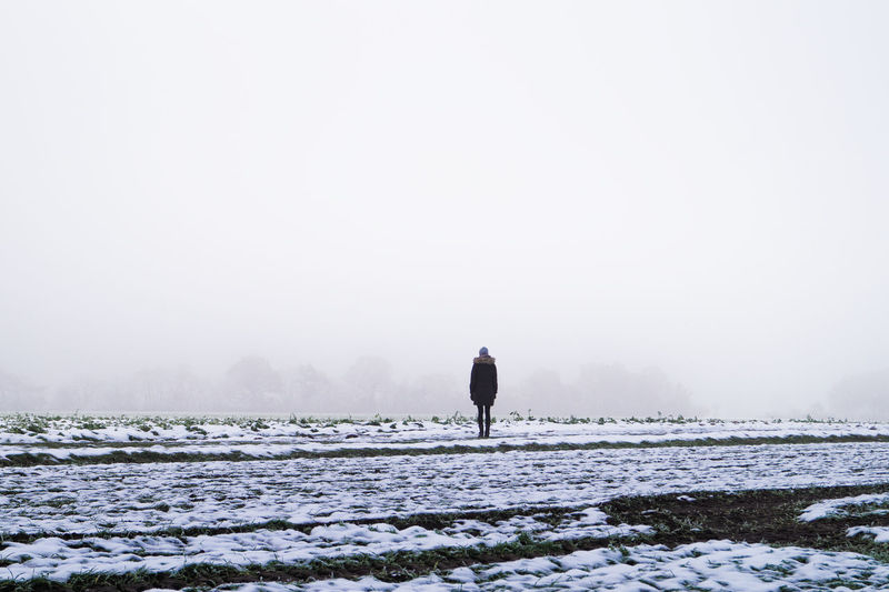 Mid Distant Rear View Of Person Standing On Snow Covered Field Against Sky During Winter
