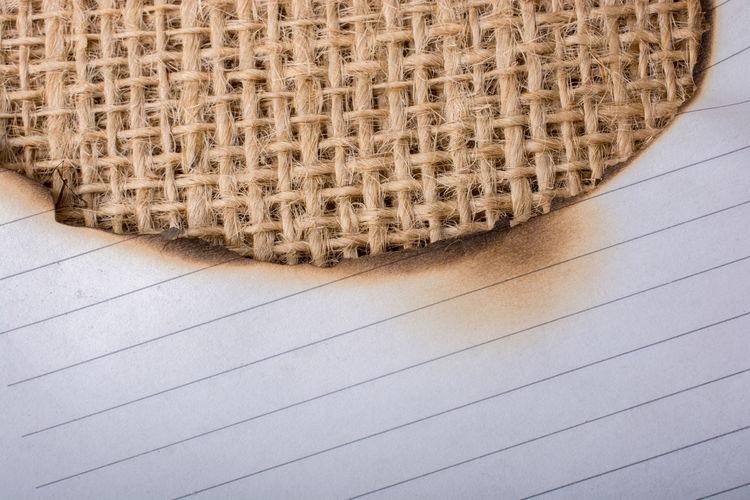 Close-up of burnt paper on burlap