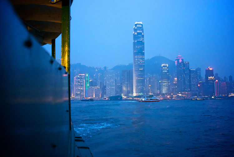 Buildings at victoria harbour in city at dusk