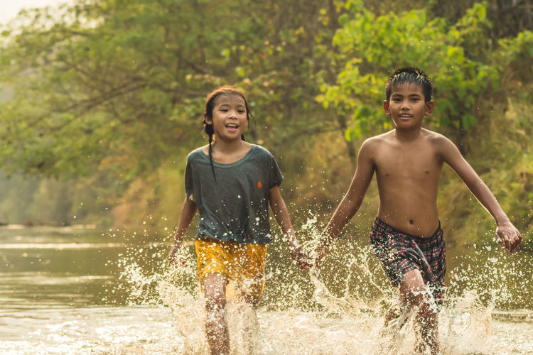 Siblings running in river