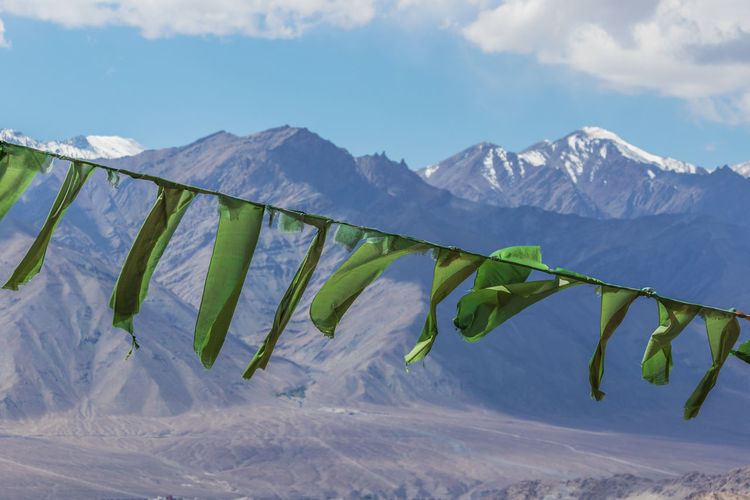 Close-up of prayer flags waving against snowcapped mountains and sky