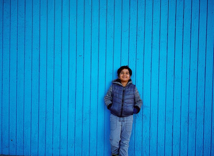 Smiling boy standing against blue wall