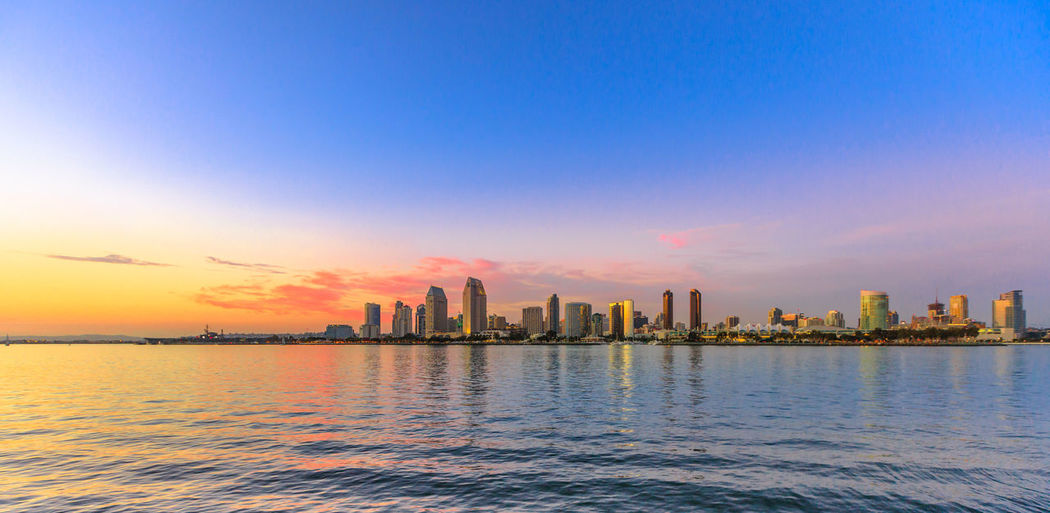Scenic landscape with sunset colors sky of San Diego skyline with skyscrapers in San Diego Bay. Districts of Waterfront Marina skyline and urban downtown cityscape from Coronado Island. Coronado Coronado Beach Coronado Island Sea Beach San Diego California United States America American Skyline Seascape Cityscape Sun Dock Port Holiday Vacations Pier Architecture Water Sky Built Structure Office Building Exterior City Building Exterior Building Skyscraper Urban Skyline Sunset Landscape Waterfront Travel Destinations Nature No People Tall - High Outdoors Bay