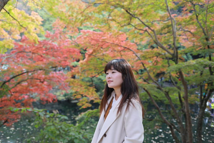 Young woman standing by trees during autumn