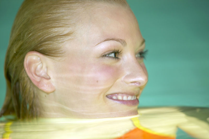 Close-Up Portrait Of Young Woman Swimming In Bath Tub
