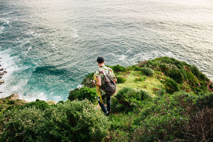 High angle view of man standing on rock by sea