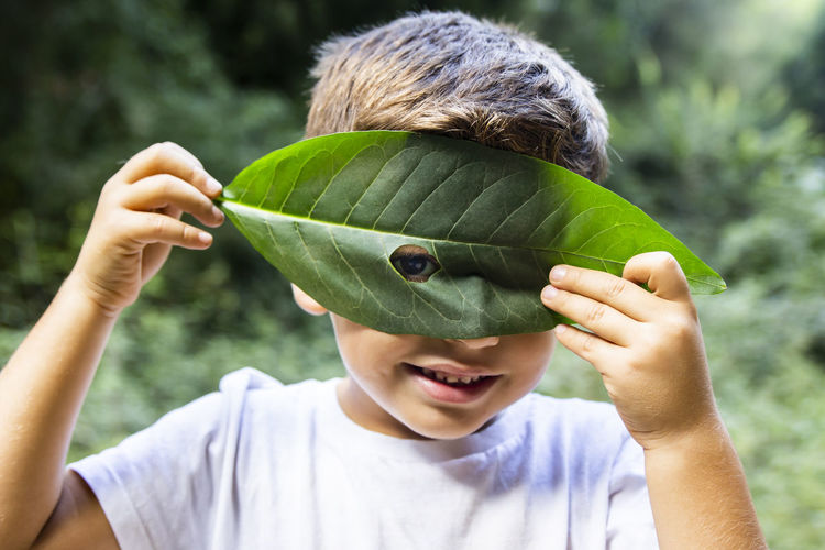 Kid looking through a leaf Boys Casual Clothing Child Childhood Day Focus On Foreground Front View Green Color Headshot Holding Innocence Leaf Leisure Activity Lifestyles Males  Men Mouth Open One Person Outdoors Portrait Real People Teenage Boys