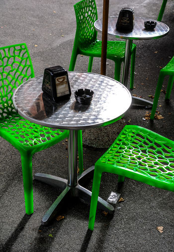 High angle view of empty chairs and table at sidewalk cafe