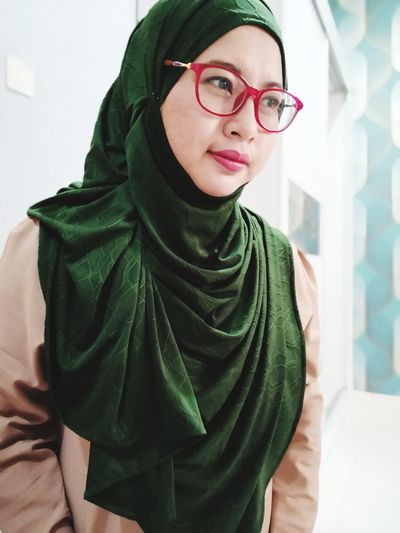 Woman wearing hijab and eyeglasses looking away in city