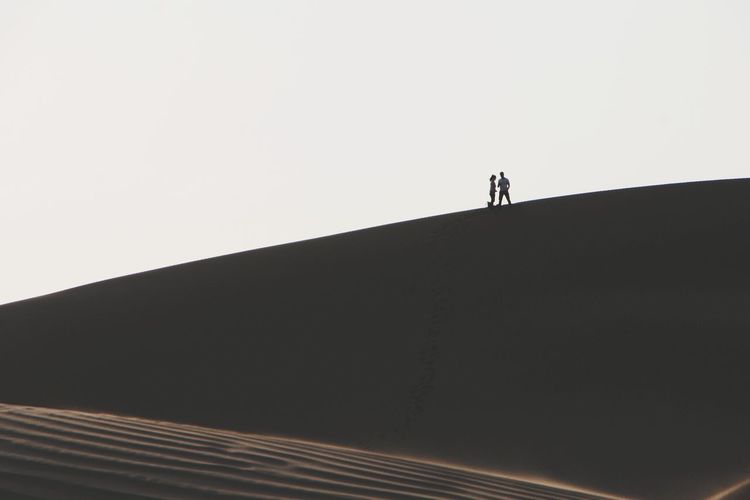 Low angle view of silhouette man standing on building against clear sky