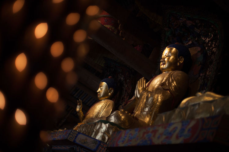 Golden buddha statues in illuminated temple