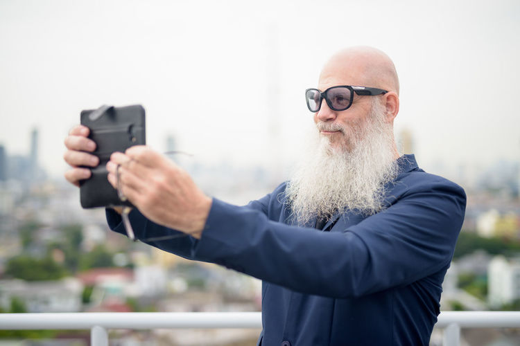 Portrait of man holding camera while standing outdoors
