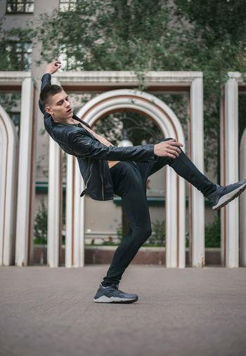 Full Length Of Young Man Dancing On Walkway