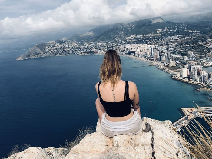 Rear view of woman sitting on cliff against cityscape