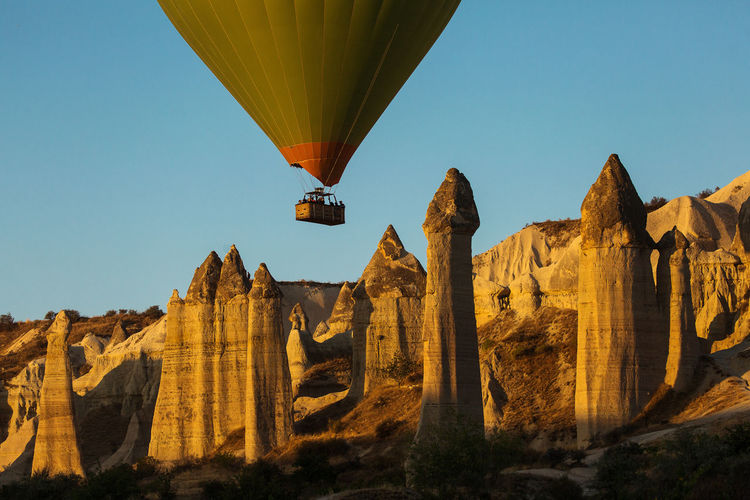 Low angle view of hot air balloon flying over rock formations