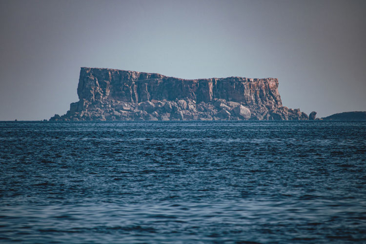 View of rock formations in sea against sky