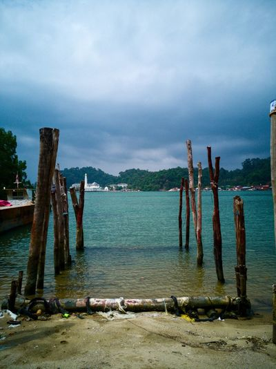 Simple wooden pillars that look like the entrance into a magical world where adventure awaits~ Sea Water Beach Outdoors Cloud - Sky No People Day Nature Wooden Pillars Pangkor Pangkor Island Malaysia HuaweiMate9Photography Mobilephotography Nature Photography Perspectives On Nature