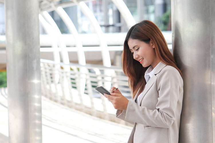 Businesswoman using phone while standing in covered bridge