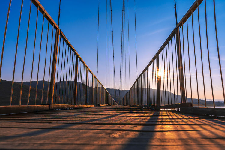 The longest suspension bridge in Bulgaria over Studen Kladenez dam with distance between the two towers of 260m. The only way to reach Lisicite village Reflection Water Sunset Nature Sky Bridge Travel Tower Lake Mountain Direction Pylon Way Suspension Dam Bulgaria Metal Overcast Wooden Suspension Bridge Longest Warm Clothing Bridge - Man Made Structure Connection Engineering Transportation Architecture Built Structure The Way Forward Sunlight Travel Destinations Tourism Cable Clear Sky Railing Outdoors Long Surface Level