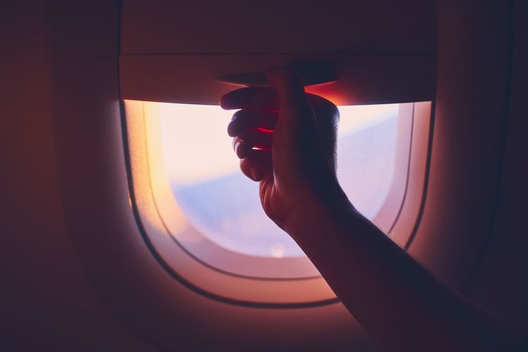 Cropped hand of person by airplane window