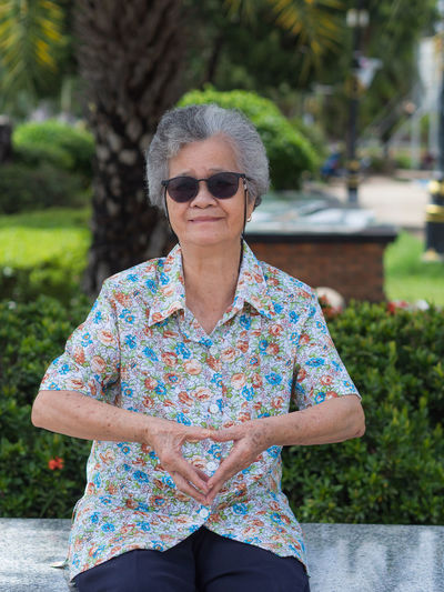 Elderly woman wears sunglasses, sitting and hands shows heart gesture in park.