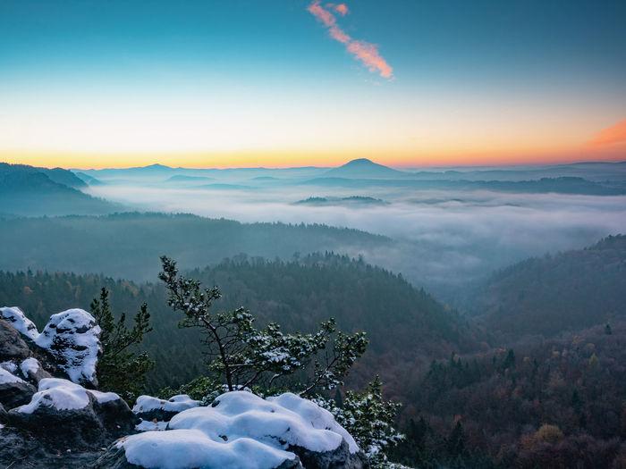 Snowy peak early morning. chill awaking in misty country. morning sun hidden bellow horizon